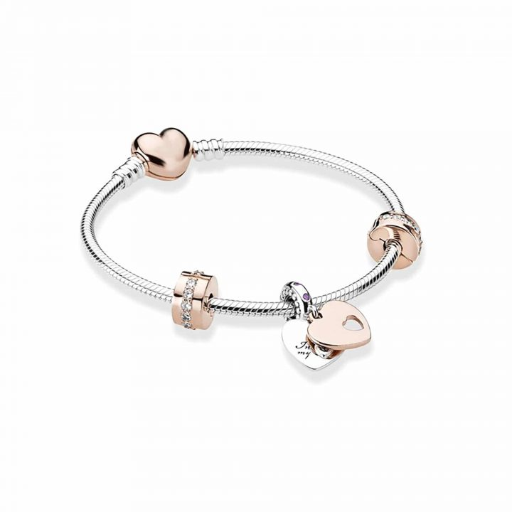 silver bracelet featuring rose gold charms, crystal stoppers and a love heart clasp fastening