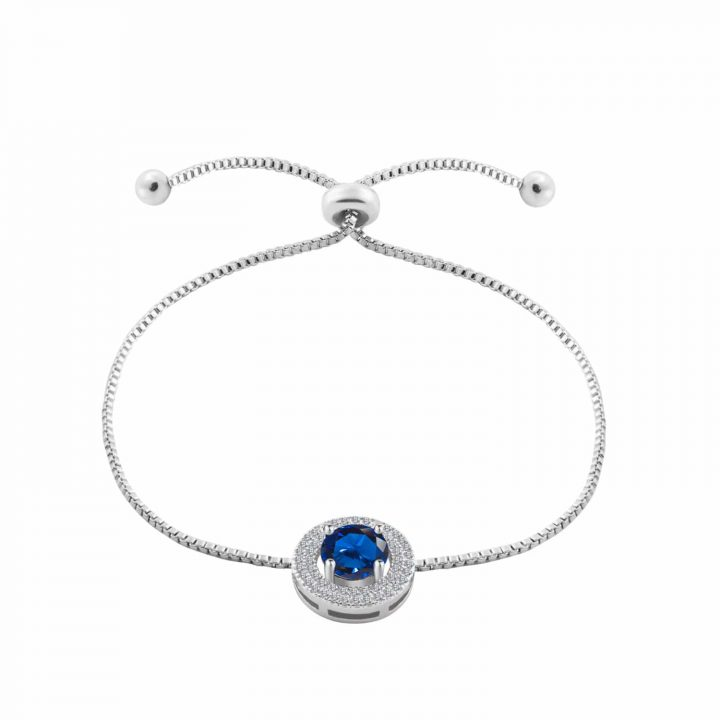 Simulated Blue Sapphire charm featuring smaller clear cut gemstones on a silver toned rhodium plated adjustable bracelet