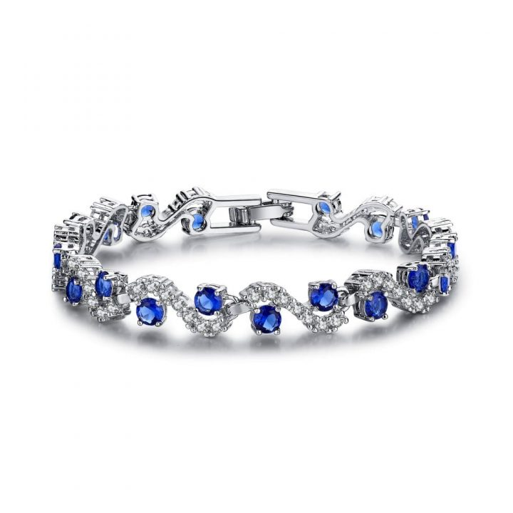Wave style silver toned bracelet featuring simulated blue sapphire and clear cut gemstones and a subtle clasp