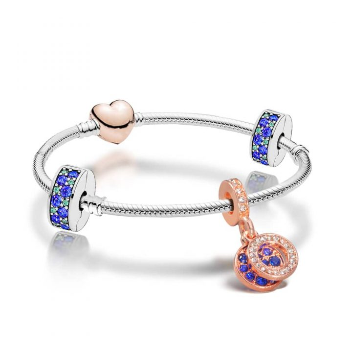 Blue and Rose Gold Plated charm Bracelet on a silver bracelet band with blue crystal charm and stoppers.